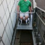 Bild des Treppenlifts mit Rollstuhlfahrer auf dem Weg nach oben.