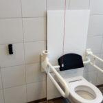 Ansicht der Toilette mit Fernbedienung an der Wand.